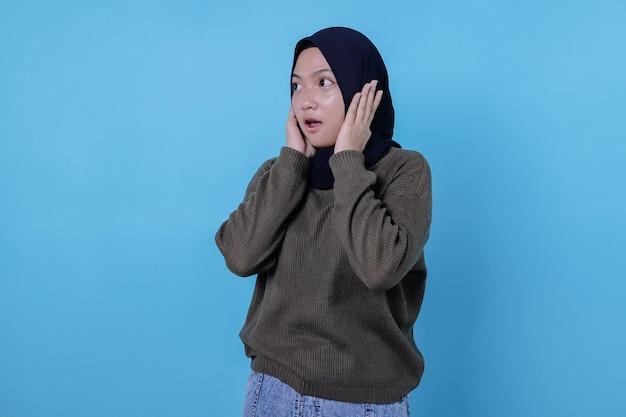 Close-up van een verward en geschokt aziatisch meisje in het dragen van hijab staart geschrokken en steekt de handen op het hoofd