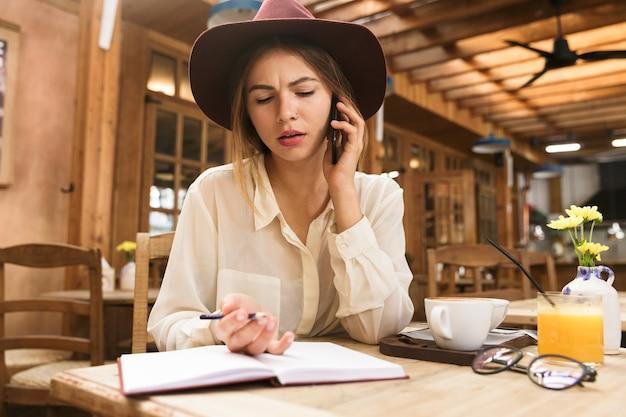 Close up van een verwarde vrouw in hoed zittend aan de café tafel