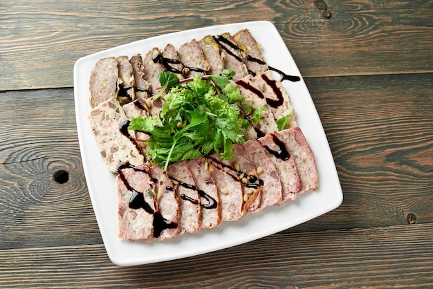 Close up van een vierkant bord vol met plakjes gevuld vlees, versierd met een groene bladeren en sojasaus op de houten tafel