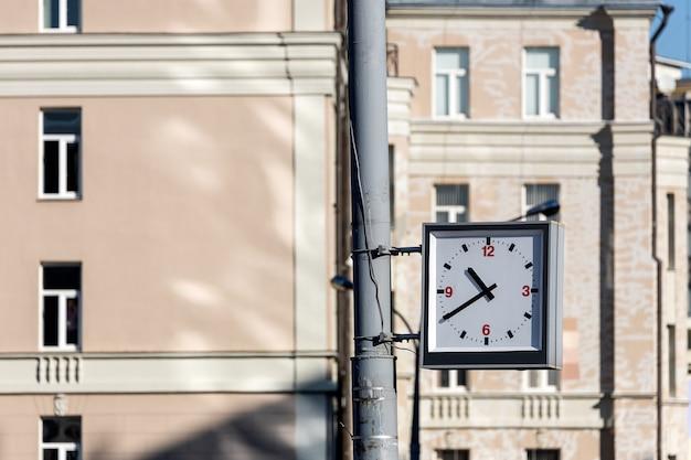 Close-up van een vierkante straatklok die aan een pilaar hangt tegen de achtergrond van een bakstenen muur van een gebouw