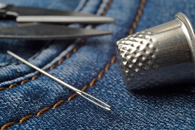 Close-up van een vingerhoed van schaar en naalden.