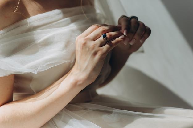 Close-up van een vintage trouwring met een blauwe diamant aan de vinger van de bruid in een glanzende trouwjurk. ochtend van de bruid. beste dag van de bruid. bruiloft accessoires.