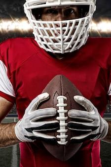 Close up van een voetballer met een rood uniform op een stadion.
