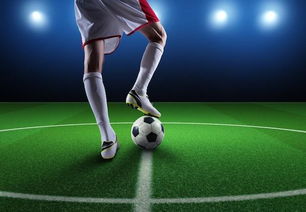 Close-up van een voetbalspeler klaar om de bal in het stadion te trappen