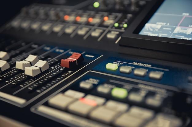 Close-up van een volumeschuifregelaar op een professionele geluidsmixer.