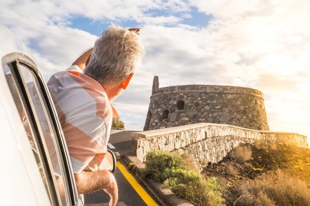 Close-up van een volwassen man buiten de auto van het raam, kijkend en genietend van het buitenleven - mensen die met de auto reizen hebben plezier Premium Foto
