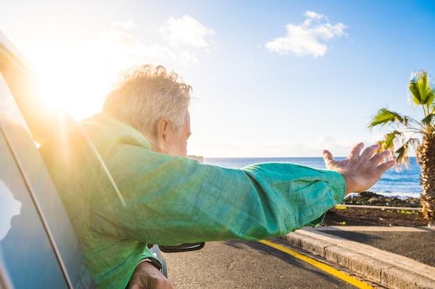 Close-up van een volwassen man buiten de auto van het raam, kijkend en genietend van het buitenleven - mensen die met de auto reizen hebben plezier