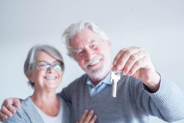 Close-up van een volwassen man met een sleutel van een nieuw huis of huis of een eigendom van beide - een paar senioren en gepensioneerden glimlachen en kijken naar de sleutel die gelukkig is