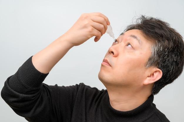 Close-up van een volwassen man oogdruppels in de ogen