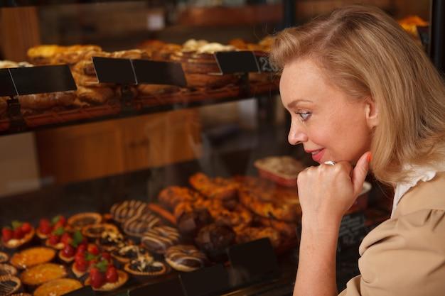 Close-up van een volwassen vrouw die desserts kiest om te kopen bij een winkel in de bakkerij