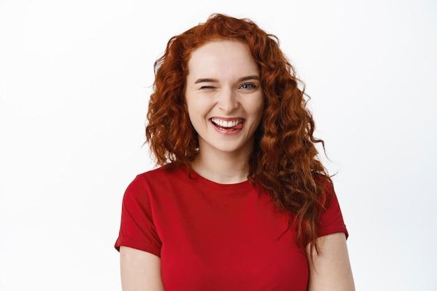 Close-up van een vrolijk, dom roodharig meisje dat tong toont, lacht met perfecte tanden en knipoogt op een witte muur