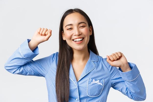 Close-up van een vrolijk lachend aziatisch meisje dat vrolijk wakker wordt en zich uitstrekt met een blij gezicht, een goede nachtrust had, zich energiek voelde vanaf de ochtend met een glimlach, witte achtergrond