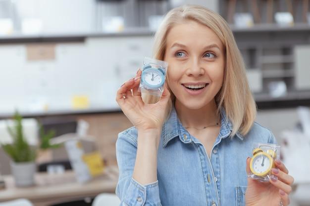 Close up van een vrolijke aantrekkelijke vrouw met twee schattige kleine wekkers, glimlachend opgewonden