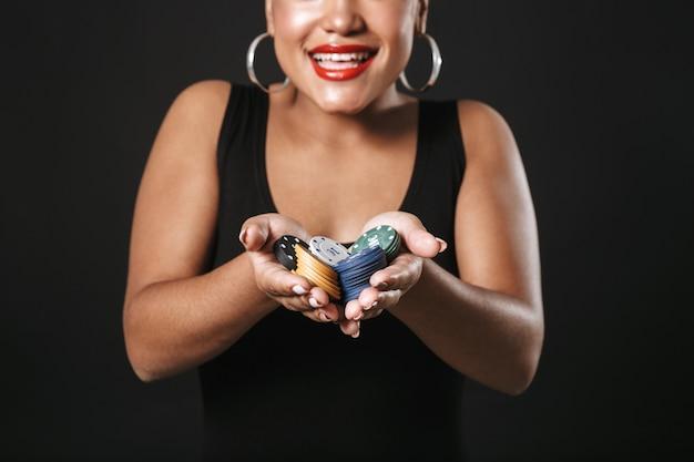 Close-up van een vrolijke afro-amerikaanse vrouw die make-up draagt ?? die zich geïsoleerd over zwarte ruimte bevindt