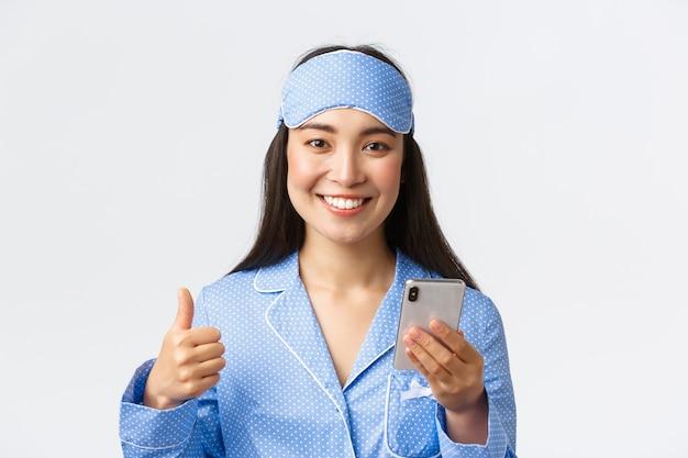 Close-up van een vrolijke glimlachende aziatische vrouw in blauwe pyjama en slaapmasker volgt haar slaap met smartphone-applicatie, toont duimen als het gebruik van een mobiele telefoon en glimlacht tevreden naar de camera.