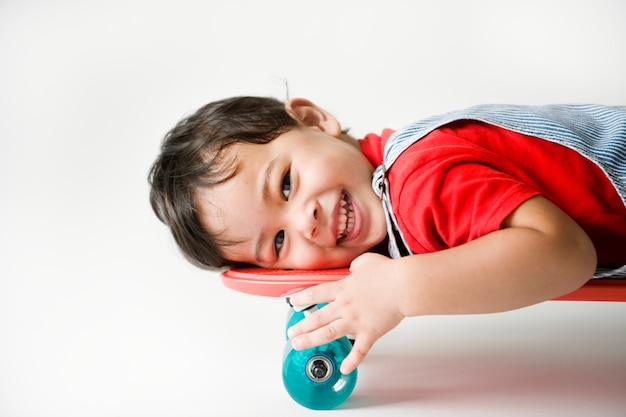 Close-up van een vrolijke jongen die op een skateboard ligt