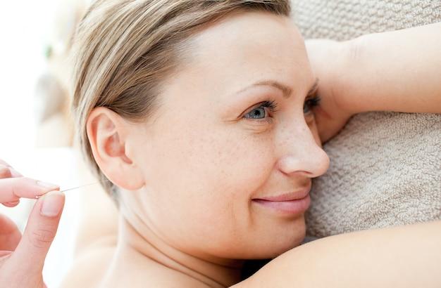 Close-up van een vrolijke vrouw in acupunctuur therapie