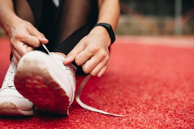 Close up van een vrouw benen schoenveters koppelverkoop op de grond in een sportpark.