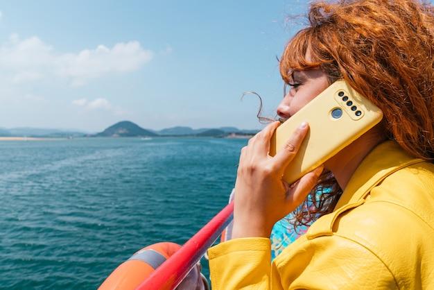 Close-up van een vrouw die aan de telefoon praat op een boot in het midden van de zee