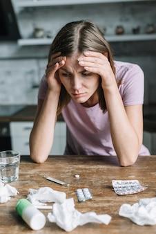 Close-up van een vrouw die aan koorts met geneesmiddelen en verfrommeld papieren zakdoekje op houten bureau lijdt