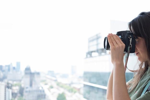 Close-up van een vrouw die beelden op dslrcamera neemt