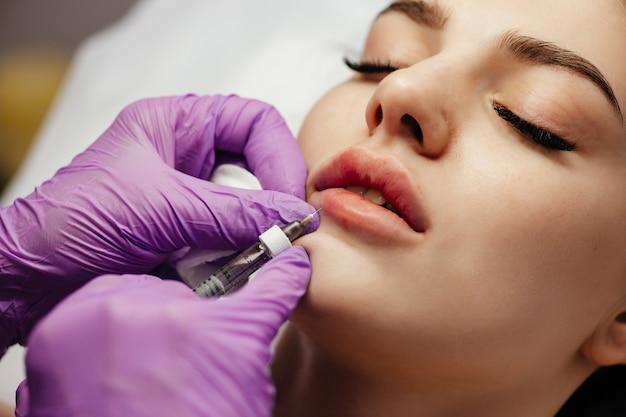 Close-up van een vrouw die botox op haar lippen krijgt