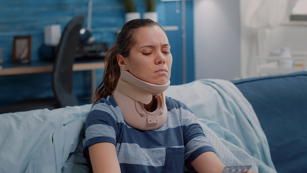 Close-up van een vrouw die cervicaal nekschuim draagt en zich ziek voelt