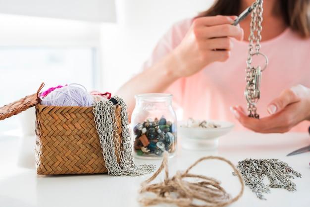 Close-up van een vrouw die de ketting en de armband met parels op wit bureau maakt
