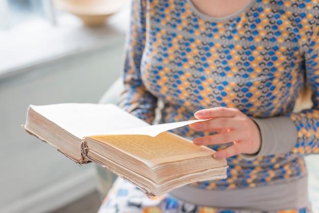 Close-up van een vrouw die de pagina van boek in haar handen draait