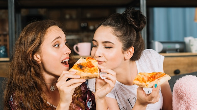 Close-up van een vrouw die de pizza van haar vriend eet