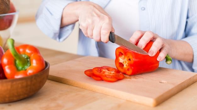 Close-up van een vrouw die de verse rode groene paprika met mes op houten hakbord snijdt