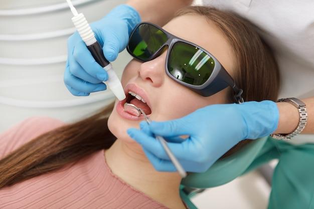 Close-up van een vrouw die een beschermende bril draagt, die tandheelkundige reiniging krijgt door professionele mondhygiënist