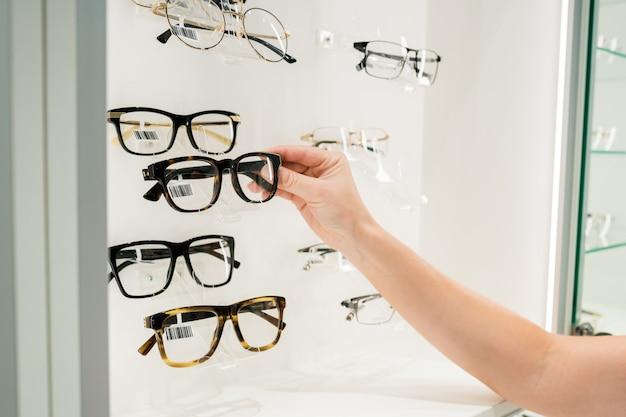 Close-up van een vrouw die een bril kiest op een brillenstandaard in een optische winkel