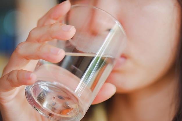 Close-up van een vrouw die een glas water vasthoudt om te drinken.
