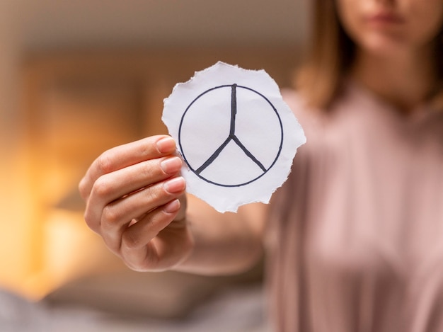 Close-up van een vrouw die een vredesteken houdt