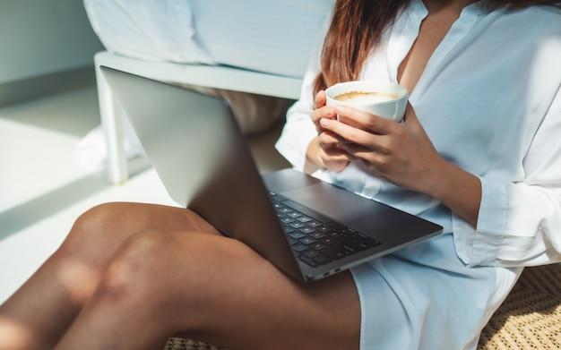 Close-up van een vrouw die en aan laptop computer gebruiken werken terwijl het drinken van koffie en thuis het zitten in slaapkamer