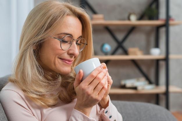 Close-up van een vrouw die geur van koffie met haar gesloten ogen neemt