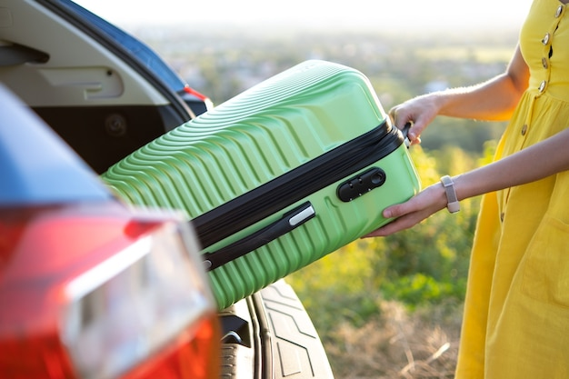 Close-up van een vrouw die groene koffer uit de kofferbak haalt. reizen en vakanties concept.