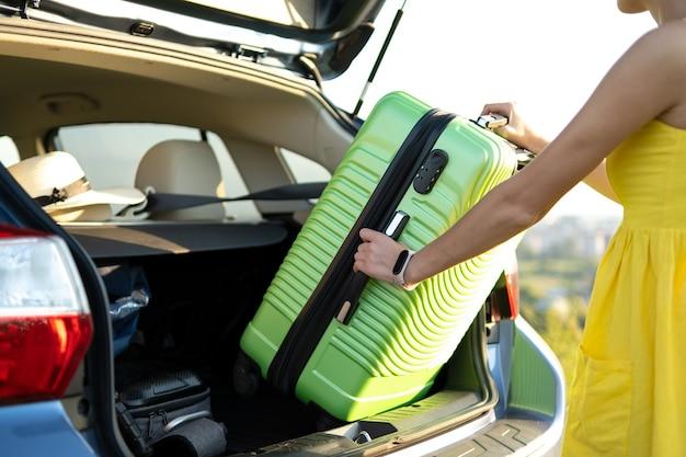Close up van een vrouw die groene koffer uit de kofferbak haalt.