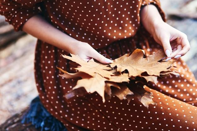 Close-up van een vrouw die herfstbladeren plukt in het bos