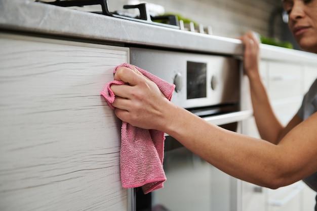 Close-up van een vrouw die het oppervlak van een elektrisch fornuis schoonmaakt.