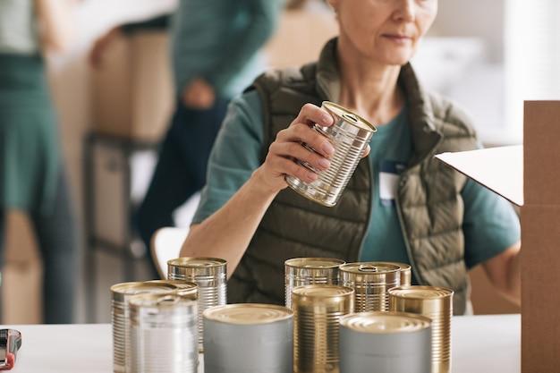 Close-up van een vrouw die ingeblikt voedsel verpakt in dozen bij liefdadigheids- en donatiesevenementen, kopieer ruimte