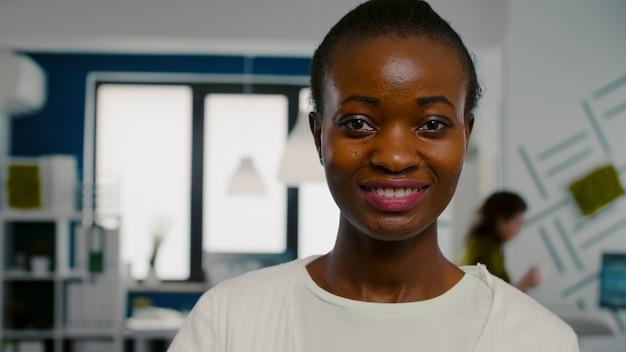Close-up van een vrouw die naar een camera kijkt die lacht terwijl ze in het kantoor van een creatief bureau staat en een laptop vasthoudt en erop typt