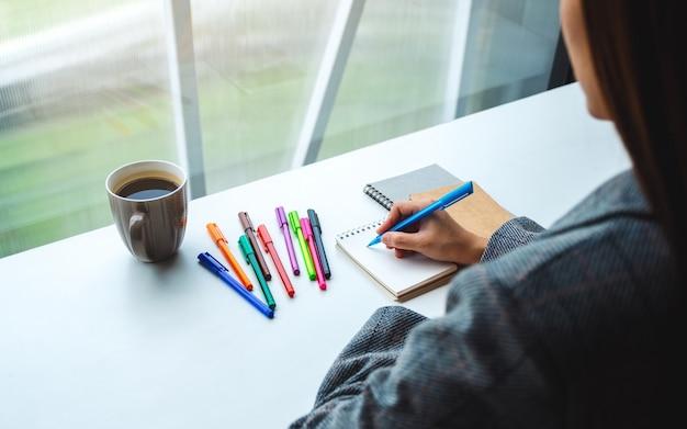 Close-up van een vrouw die op een leeg notitieboekje met gekleurde pennen en koffiekop op de lijst schrijft