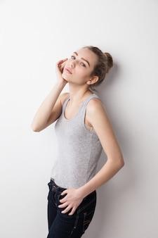 Close-up van een vrouw die tegen de muur staat en haar hand aanraakt. geïsoleerd over grijze achtergrond.