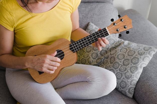 Close-up van een vrouw die ukelele in haar woonkamer speelt