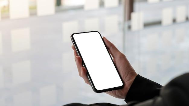 Close-up van een vrouw hand met mobiele telefoon met wit leeg scherm