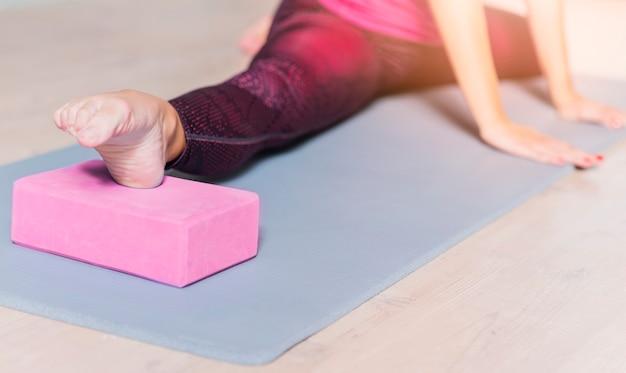 Close-up van een vrouw het praktizeren yoga die yogablok met behulp van