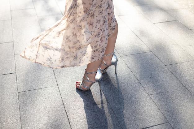 Close-up van een vrouw in een jurk en zilveren schoenen met hoge hakken die langs een verharde stadsstraat loopt. wereld toerisme dag