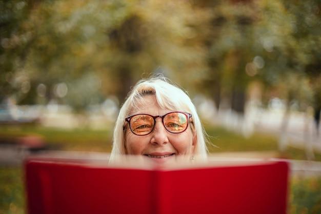 Close-up van een vrouw in glazen en vrijetijdskleding leest een boek terwijl u ontspant in het park